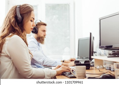 Portrait of happy businesswoman working with male colleague at computer desk in office