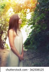 Portrait of a happy calm fashion woman dressed in white dress illuminated by sunlight standing on a forest way.
