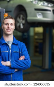 Portrait of happy car mechanic with arms crosses in workshop