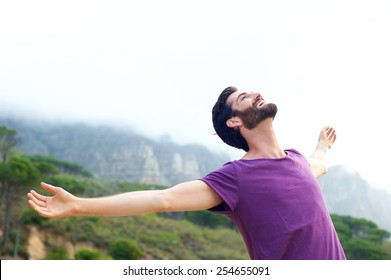 Portrait of a happy carefree man smiling with arms open outdoors