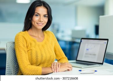Porträt einer glücklichen Geschäftsfrau im Pullover, die an ihrem Arbeitsplatz sitzt