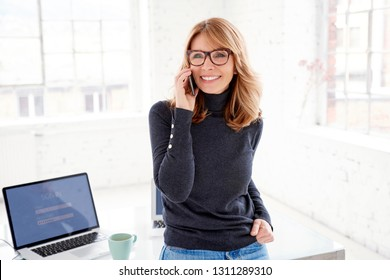 Portrait of happy casual businesswoman using her mobile phone and making a call while standing in the office.