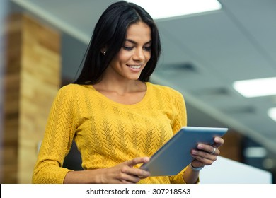 Portrait of a happy casual businesswoman using tablet computer in office