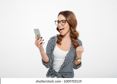 Portrait of a happy casual girl looking at mobile phone and celebrating isolated over white background