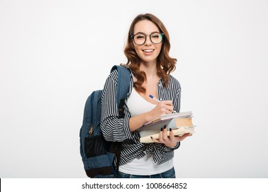 Portrait of a happy casual girl student with backpack writing in a notepad while standing with books isolated over white background