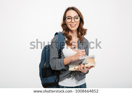 feec1dabbb Portrait of a happy casual girl student with backpack writing in a notepad  while standing with