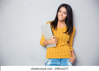 Portrait of a happy casual woman holding laptop over gray background and looking at camera