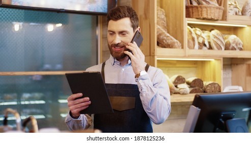 Portrait of happy Caucasian bearded handsome male baker standing in own bakery, tapping on tablet device and speaking on smartphone. Male worker talking on mobile phone with client. Bakehouse concept