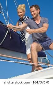 Portrait of a happy caucasian couple on a sailing boat - sailing trip.