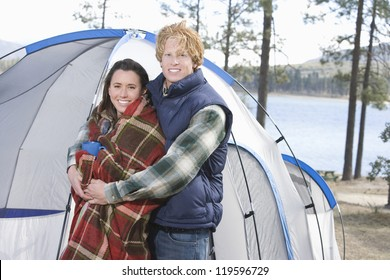 Portrait of a happy Caucasian couple standing in front of the campaign tent