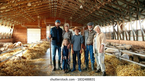Portrait of happy Caucasian family of three generations standing in shed with livestock and smiling. Old parents with children and grandchildren in stable. Farmers with kids at farm.