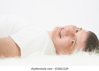 Portrait of happy Caucasian handsome man lying on floor and smiling. Horizontal image