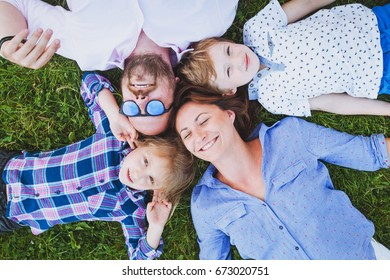 portrait of happy caucasian smiling family with two kids lying on the grass, top view