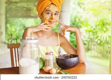 Portrait of a happy caucasian woman using natural secrets to do a skin care (ingredients are on a table: oats, flour, eggs, leaves)
