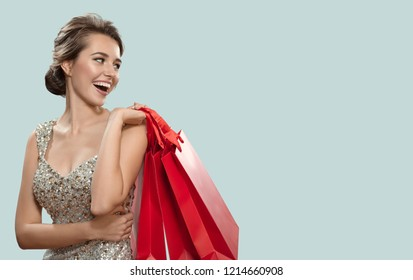 Portrait of happy charming woman holding red shopping bags. Blue background.