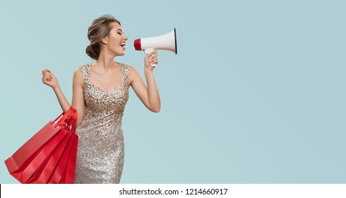 Portrait of happy charming woman holding red shopping bags. Shout into megaphone on copyspace. Blue background.
