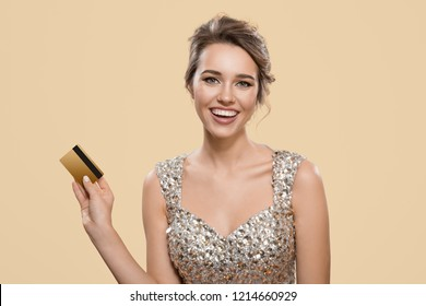 Portrait of happy charming woman holding gold plastic bank card. Yellow background.
