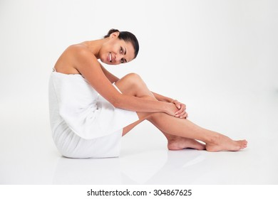 Portrait of a happy charming woman in towel sitting on the floor isolated on a white background. Looking at camera