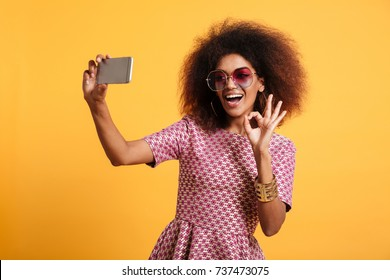 Portrait of a happy cheerful afro american woman in retro style clothes showing ok gesture while standing and taking a selfie isolated over yellow background