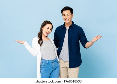 Portrait of happy cheerful awesome Asian couple with big smiles opening hands on isolated light blue background