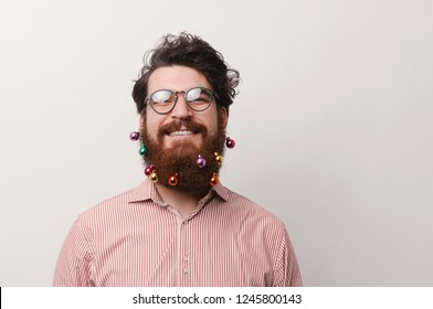 Portrait of happy cheerful bearded man with decorated beard for christmas holidays