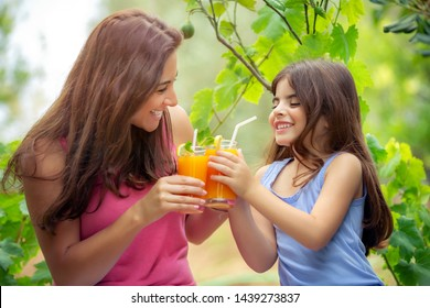 Portrait of a happy cheerful family drinking orange juice on the picnic in the garden in sunny day, mother and daughter with fresh drink, happy summer weekend