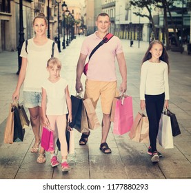 Portrait of happy cheerful family of four people happily shopping together in the city