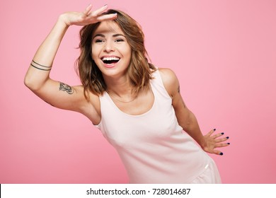 Portrait of a happy cheerful girl in summer clothes looking far away with hand at her forehead isolated over pink background