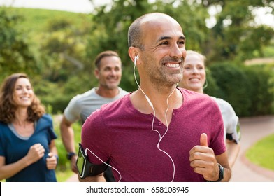 Portrait of a happy cheerful man listening to music while jogging. Man listening to music while jogging with group. Happy trainer in park running with team.