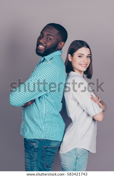 Portrait of happy cheerful multiethnic couple standing back to back with crossed hands