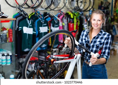 Portrait of happy cheerful positive  woman who is standing with new bicycle indoors.