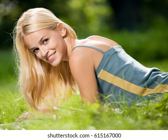 Portrait of happy cheerful smiling young beautiful blond woman, outdoors