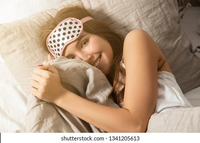 Portrait of happy cheerful woman lying in bed wearing sleeping mask. Model in white nightgown under blanket resting and looking at camera with happiness. Bedroom interior