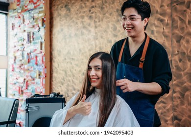 Portrait of happy and cheerful young female customer showing thumbsup sign with male hairdresser wearing apron styling hair