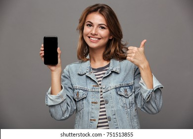 Portrait of a happy cheery teenage girl dressed in denim jacket holding blank screen mobile phone and showing thumbs up gesture isolated over gray background