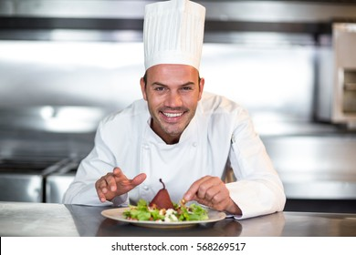 Portrait of happy chef garnishing food in a commercial kitchen