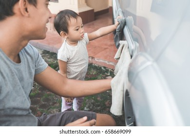 portrait of happy child being a little helper by helping her daddy cleaning up the car