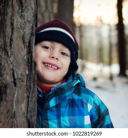 Portrait of a happy child boy in winter forest leaning agaist a tree trunk, low evening light, bokeh in background.