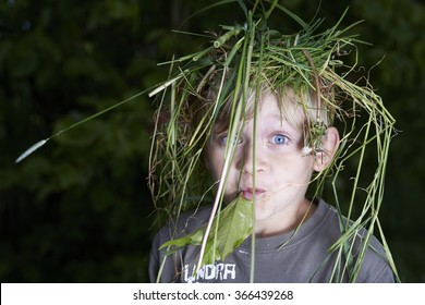 portrait of a happy child boy with wreath of grass on head