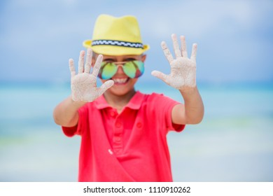 Portrait of happy child boy in yellow hat and sunglasses on beach. Summer vacation concept