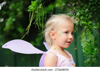 Portrait of a happy child, cute adorable little girl in a fairy costume with fairy wings on her birthday