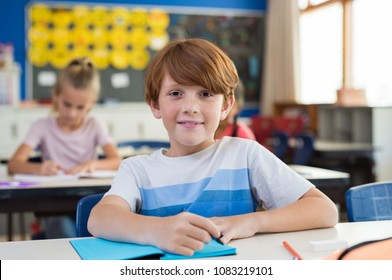 Portrait of happy child with freckles sitting at school desk in class room. Young boy smiling in class and looking at camera. Pupil with red hair writing on notebook at elementary school. Education.