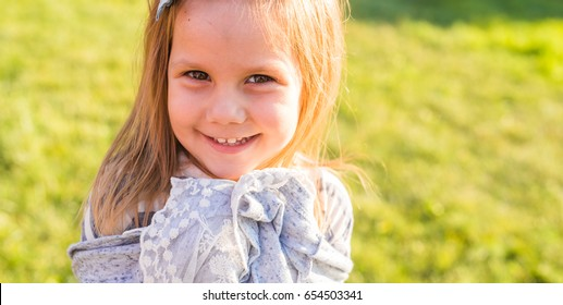 Portrait of happy child girl playing in summer in nature
