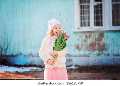 portrait of happy child girl with tulips on the walk in early spring