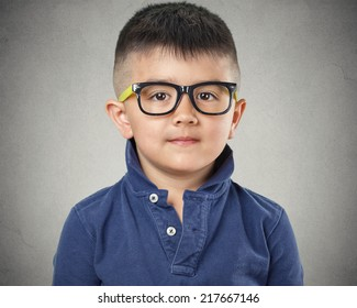 Portrait happy child with glasses on grey wall background. Face expressions
