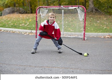 A portrait of happy child play hockey outside