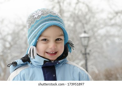 Portrait of a happy child in winter park with falling snow.