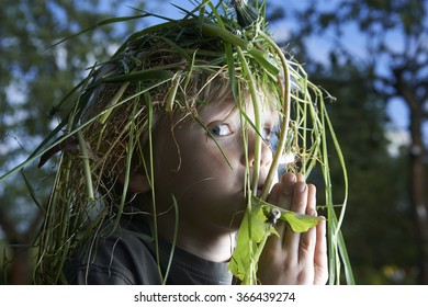 portrait of a happy child with Wreath of green grass on head