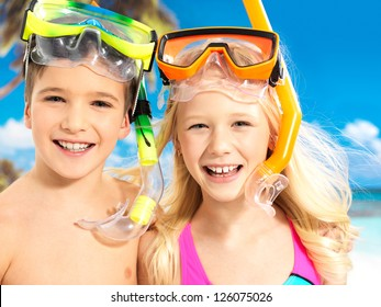 Portrait of the happy children enjoying at beach.  Brother and sister standing together in swimwear with swimming mask on head .