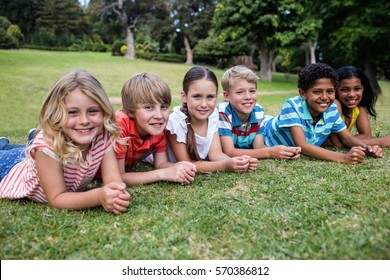 Portrait of happy children lying on grass in park